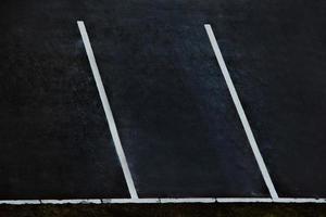 estacionamento vazio. marcações brancas para carros em asfalto preto. foto