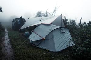 acampar em um dia nublado e chuvoso na floresta foto