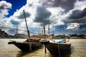 barco de pesca tradicional na margem do rio sob céu nublado foto
