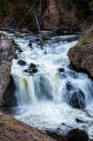 cachoeira fluindo em movimento embaçado sobre o rio de rocha negra. foto