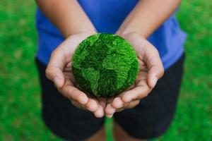 mãos de mulheres segurando terra sobre fundo verde foto