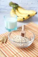 flocos de aveia, copo de leite e banana na mesa foto