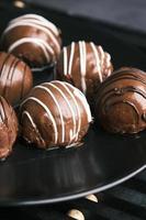 chocolate amargo de formato redondo em um prato no fundo rosa foto