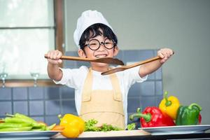 filho de menino asiático cozinhando salada foto