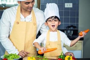 mulher asiática jovem mãe com filho menino cozinhando salada foto