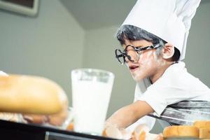 menino asiático usa óculos para provocar papai cozinhando foto