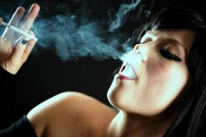 jovem linda mulher fumando cigarro foto