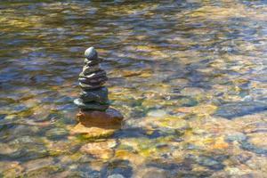 pilha de pedras lindamente empilhadas no rio foto