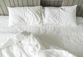 Cama com aro com decoração de travesseiro branco bagunçado no interior do quarto foto