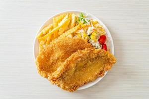 peixe com batatas fritas com mini salada no prato branco foto