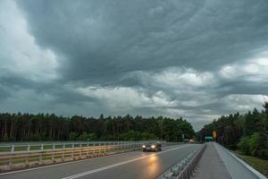 carro andando na rua antes da tempestade foto