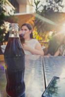 garrafa de vidro de refrigerante de cola gelado na mesa de metal foto