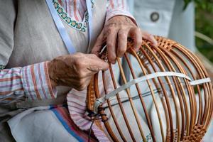 velha em traje nacional fazer cesta de vime local. foto