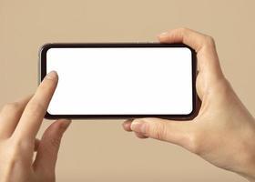 pessoa segurando o telefone móvel com tela branca. foto
