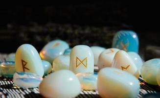 close-up de pedras rúnicas na mesa de madeira. atributos ocultos foto