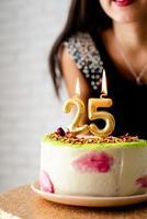 mulher caucasiana em vestido de festa preto acendendo velas no bolo de aniversário foto