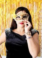 mulher com vestido de festa preto com máscara de baile de máscaras dourada foto