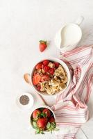 café da manhã saudável, cereais, frutas frescas e leite em uma tigela, vista de cima foto