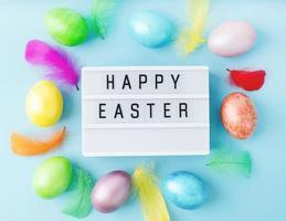Feliz Páscoa, caixa de luz decorada com penas e ovos de cores vivas foto