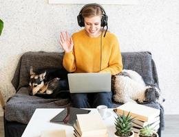 mulher com fones de ouvido pretos estudando on-line usando um laptop e dizendo olá foto