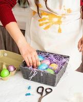 mulher com suéter vermelho e avental branco decorando ovos de páscoa coloridos foto