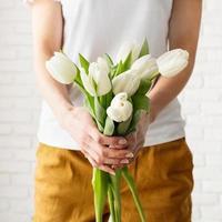 mulher com roupas amarelas segurando um buquê de tulipas brancas foto