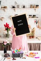 mulher de vestido rosa segurando um quadro de papel preto com palavras feliz páscoa foto