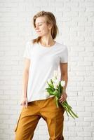 jovem vestindo uma camiseta branca em branco segurando flores de tulipas foto