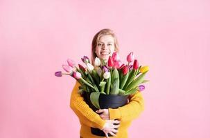 mulher segurando um balde de tulipas frescas isoladas em um fundo rosa foto