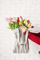 mão de uma mulher segurando uma bolsa de tecido de bolinhas cinza com tulipas coloridas foto