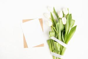 flores de tulipa e cartão em branco com vista superior do envelope foto