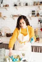 mulher colorindo ovos de páscoa de azul na cozinha foto