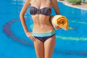 mulher bronzeada na praia de verão segurando uma toalha na mão na piscina foto