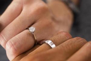 joias luxuosas de anel de diamante de noivado de mãos dadas foto