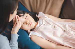 menina asiática doente dormindo no sofá foto