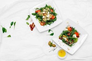 dois pratos brancos com saladas em um fundo branco foto
