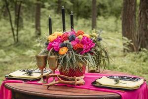 mesa de madeira decorada com flores, velas, utensílios foto
