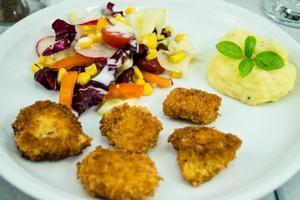nuggets de frango frito dourado com salada foto