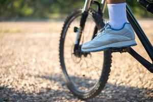 uma perspectiva baixa de ciclistas de montanha em um caminho rochoso com foco em sapatos foto