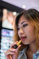 bela jovem selecione a cor de batom para comprar no shopping foto