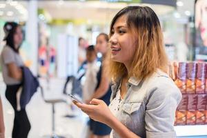 jovem mulher bonita vestindo mensagens de texto de jaqueta jeans no smartphone. foto