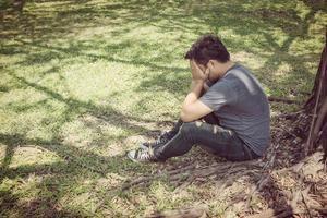 jovem triste sentado no parque foto