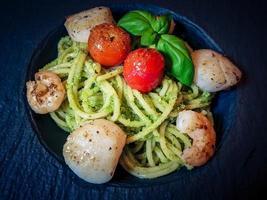 conchas de água salgada fritas no espaguete com pesto verde foto