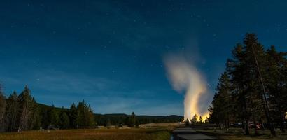 erupção do velho e fiel gêiser no parque nacional de yellowstone à noite foto