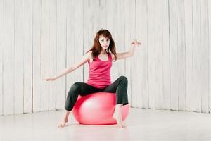 menina bonita dançando em um fitball rosa, borrão de movimento, tonalidade alta foto