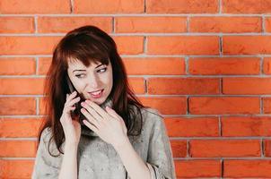 linda mulher falando ao celular, sorrindo, parede de tijolos ao fundo foto