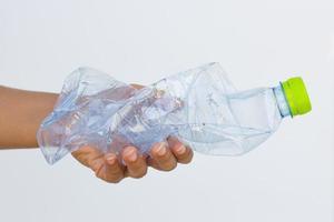 mão segurando uma garrafa de plástico usada foto