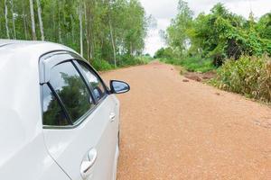 carro branco pára na estrada na estrada de terra e cascalho foto