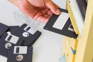 mão inserindo um disquete de 3,5 polegadas em uma unidade de disquete foto