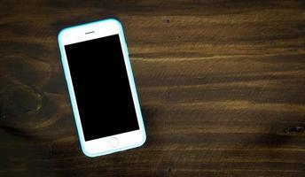 telefone inteligente em cima da mesa com fundo de madeira, tom escuro foto
